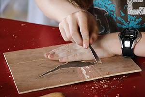 enfant qui grave une plaque de bois